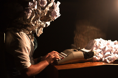Man with paper head using typewriter